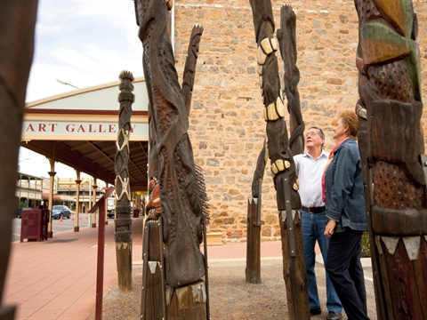 Man and Woman looking at the Story Poles located at the exterior of the Gallery