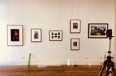 Image of artworks being hung for installation of a show